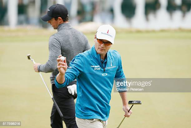 Zach Johnson of the United States celebrates a birdie putt on the 11th green as Rory McIlroy of Northern Ireland looks on during the round of 16 in...