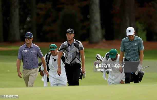 Zach Johnson of the United States, Danny Willett of England and Jordan Spieth of the United States walk up the 18th fairway during a practice round...