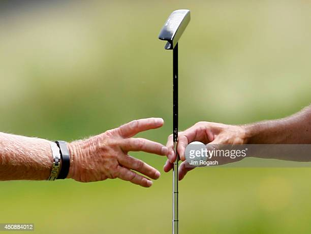 Zach Johnson of the United States hands his putter and golf ball to his caddie Damon Green during the first round of the Travelers Championship golf...