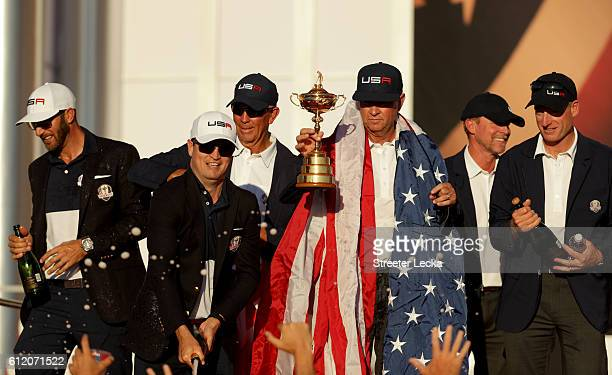 Zach Johnson of the United States sprays champagne as captain Davis Love III holds the Ryder Cup during the closing ceremony of the 2016 Ryder Cup at...
