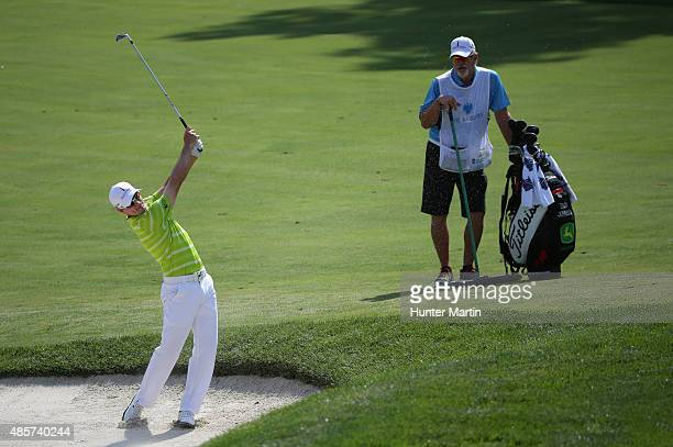 Zach Johnson of the United States watches hits a bunker shot on the fifth hole as his caddie Damon Green looks on during the third round of The...