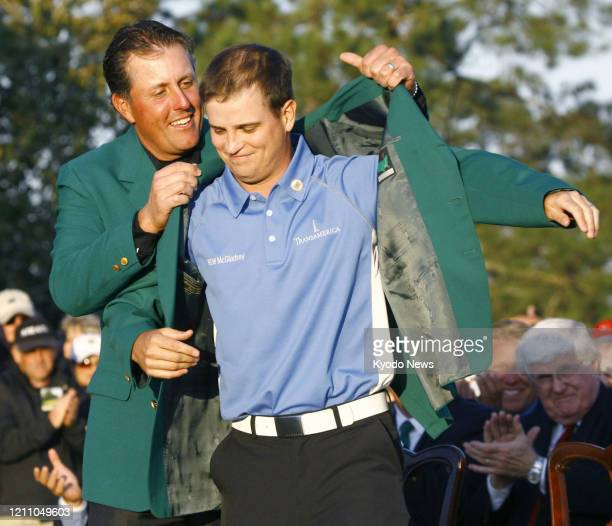 Zach Johnson receives the Masters green jacket from US compatriot Phil Mickelson after winning the tournament in Augusta Georgia on April 8 2007