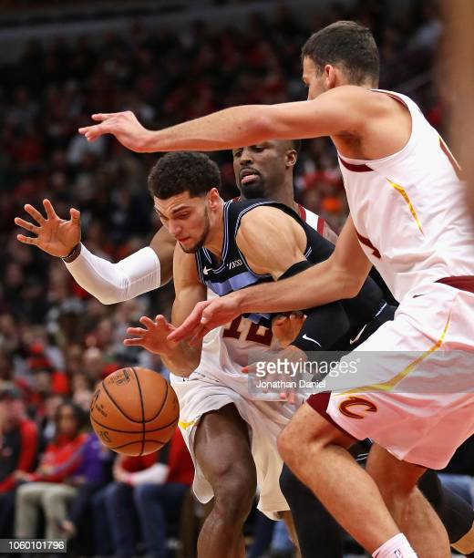 Zach LaVine of the Chicago Bulls drives between David Nwaba and Ante Zizic of the Cleveland Cavaliers at the United Center on November 10 2018 in...