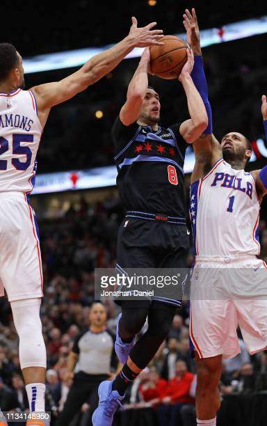 Zach LaVine of the Chicago Bulls goes up for the gamewinning shot against Ben Simmons and Mike Scott of the Philadelphia 76ers at the United Center...