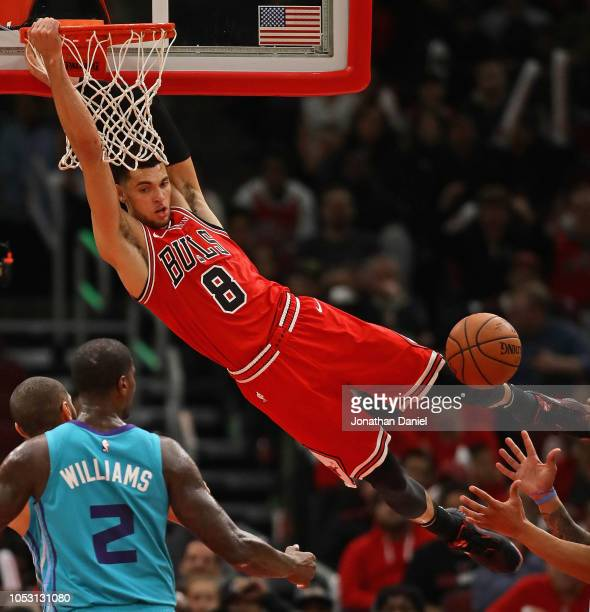 Zach LaVine of the Chicago Bulls hangs onto the rim after a second half dunk against the Charlotte Hornets at the United Center on October 24 2018 in...