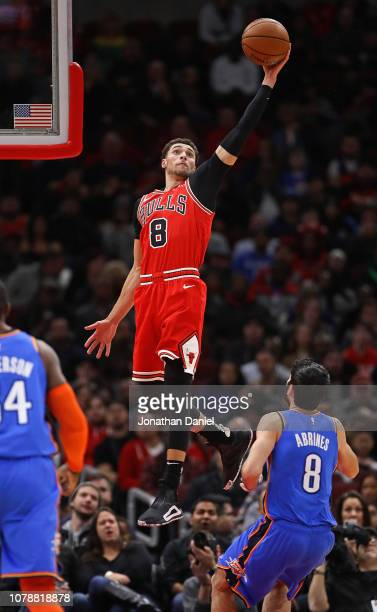 Zach LaVine of the Chicago Bulls leaps high over Alex Abrines of the Oklahoma City Thunder to catch a pass at the United Center on December 07 2018...