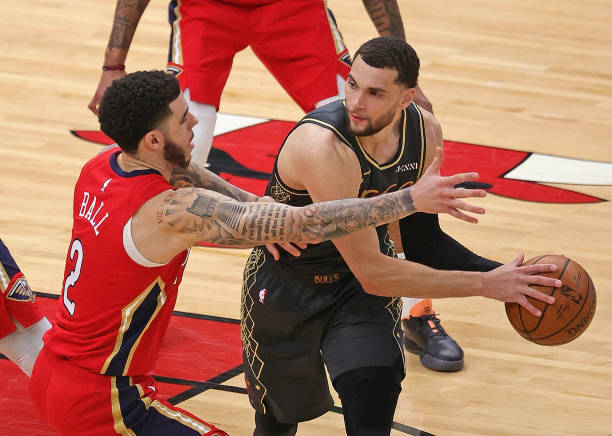 Zach LaVine of the Chicago Bulls looks to pass under pressure from Lonzo Ball of the New Orleans Pelicans at the United Center on February 10, 2021...
