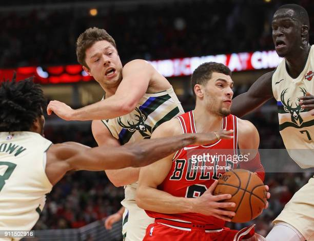 Zach LaVine of the Chicago Bulls moves between Sterling Brown Matthew Dellavedova and Thon Maker of the Milwaukee Bucks at the United Center on...