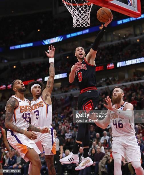 Zach LaVine of the Chicago Bulls puts up a shot between Jonah Bolden Kelly Oubre Jr #3 and Aron Baynes of the Phoenix Suns at the United Center on...
