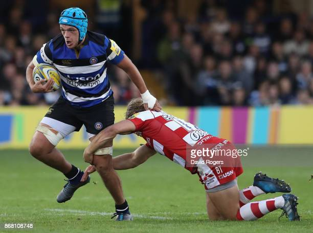 Zach Mercer of Bath is held by Richard Hibbard during the Aviva Premiership match between Bath Rugby and Gloucester Rugby at the Recreation Ground on...