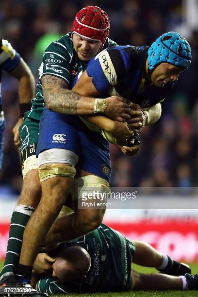Zach Mercer of Bath Rugby is tackled by Sebastien de Chaves and Ben Franks of London Irish during the Aviva Premiership match between London Irish...