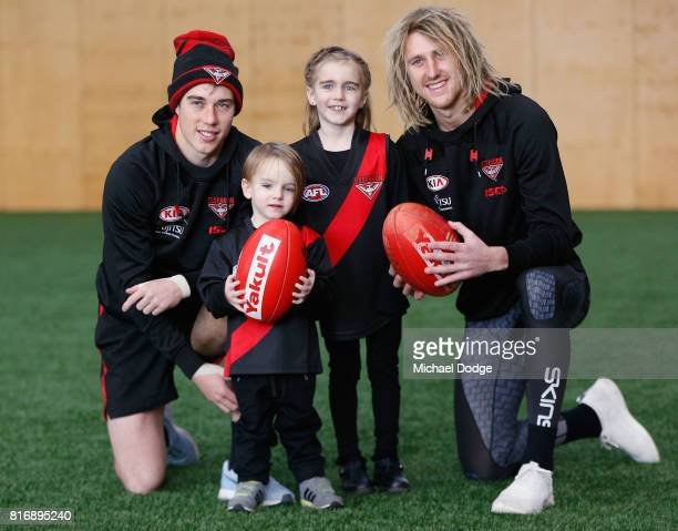 Zach Merrett and Dyson Heppell of the Bombers pose with young fans from childrens cancer charity Challenge during an Essendon Bombers AFL media...