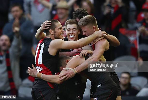 Zach Merrett Matthew Leuenberger Orazio Fantasia of the Bombers and their teammates celebrate winning at the final siren during the round 21 AFL...