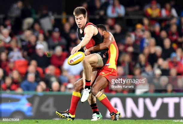 Zach Merrett of the Bombers gets a kick away during the round 22 AFL match between the Gold Coast Suns and the Essendon Bombers at Metricon Stadium...