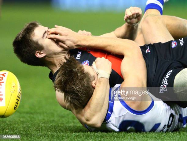 Zach Merrett of the Bombers grapples with Mason Wood of the Kangaroos after being tackled during the round 15 AFL match between the Essendon Bombers...
