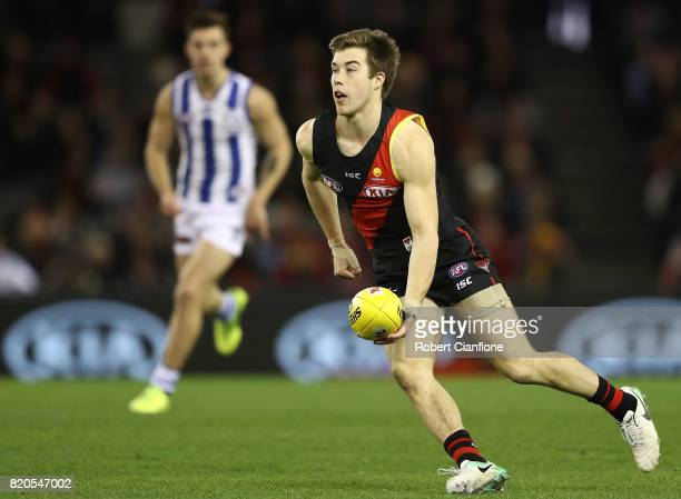 Zach Merrett of the Bombers handballs during the round 18 AFL match between the Essendon Bombers and the North Melbourne Kangaroos at Etihad Stadium...