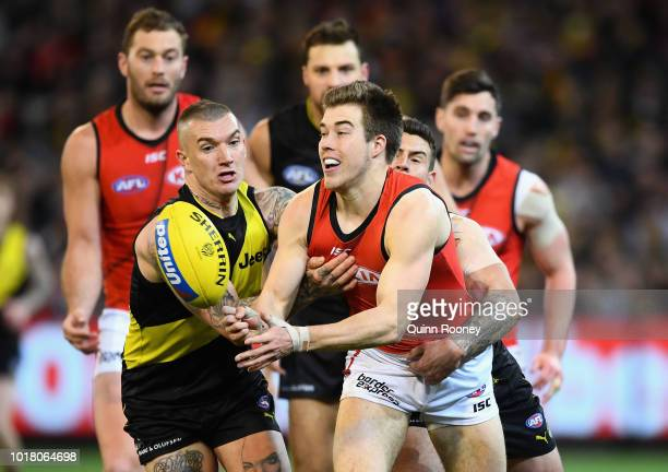Zach Merrett of the Bombers handballs whilst being tackled by Dustin Martin of the Tigers during the round 22 AFL match between the Richmond Tigers...