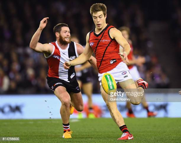 Zach Merrett of the Bombers kicks whilst being tackled by Jack Steven of the Saints during the round 17 AFL match between the St Kilda Saints and the...