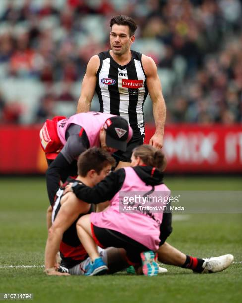 Zach Merrett of the Bombers lays on the ground after an off the ball hit from Levi Greenwood of the Magpies who watches on during the 2017 AFL round...
