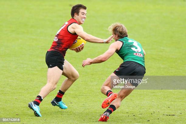 Zach Merrett of the Bombers runs past Darcy Parish during an Essendon Bombers AFL training session at The Hangar on March 20 2018 in Melbourne...