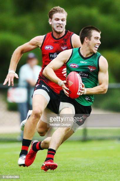 Zach Merrett of the Bombers runs with the ball from Michael Hurley of the Bombers during the Essendon Bombers AFL IntraClub Match at The Hangar on...