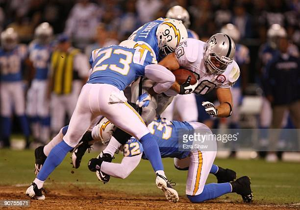 Zach Miller of the Oakland Raiders is tackled after he made a reception by Quentin Jammer Kevin Burnett and Eric Weddle of the San Diego Chargers on...