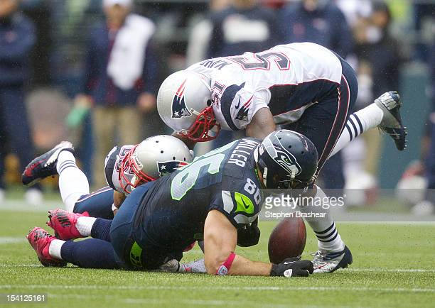 Zach Miller of the Seattle Seahawks fumbles the ball after a hit by Jerod Mayo and Patrick Chung of the New England Patriots during a game at...