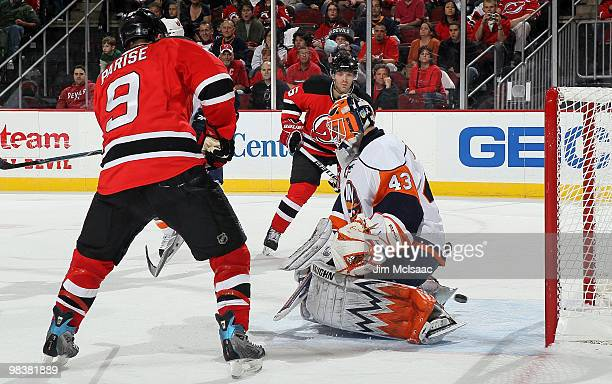 Zach Parise and Andy Greene of the New Jersey Devils watch a shot from teammate Patrik Elias get by Martin Biron of the New York Islanders for a...
