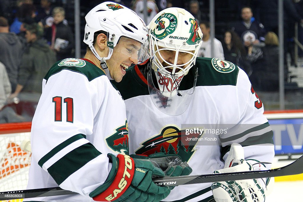 Zach Parise #11 and goaltender Ilya Bryzgalov #30 of the Minnesota Wild share a laugh following a 1-0 victory over the Winnipeg Jets at the MTS Centre on April 7, 2014 in Winnipeg, Manitoba, Canada.