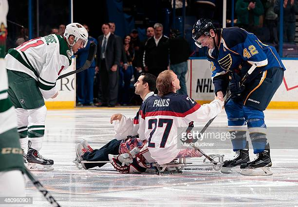 Zach Parise of the Minnesota Wild and David Backes of the St Louis Blues greet paralympic sled hockey team members Josh Pauls and Steve Cash prior to...