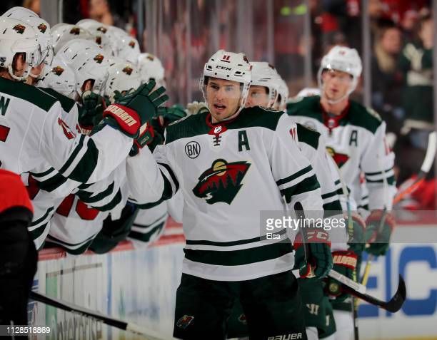 Zach Parise of the Minnesota Wild celebrates his goal with teammates on the bench in the second period against the New Jersey Devils at Prudential...