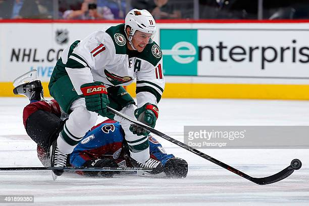 Zach Parise of the Minnesota Wild controls the puck against Erik Johnson of the Colorado Avalanche at Pepsi Center on October 8 2015 in Denver...