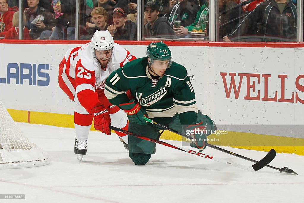 Zach Parise #11 of the Minnesota Wild controls the puck as he falls to the ice with Brian Lashoff #23 of the Detroit Red Wings defending during the game on February 17, 2013 at the Xcel Energy Center in Saint Paul, Minnesota.