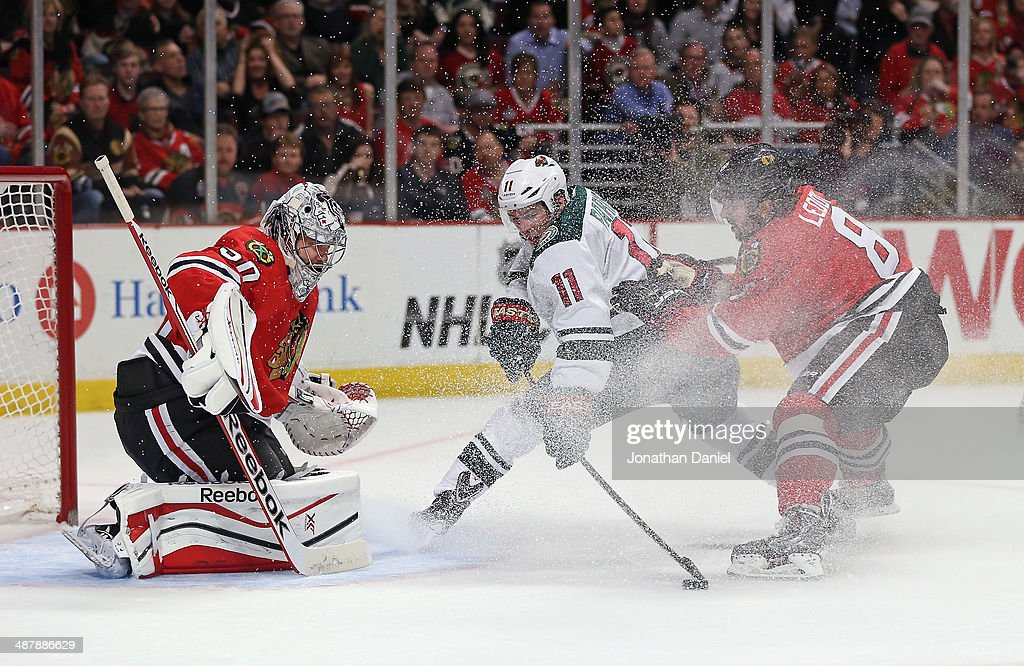 Zach Parise #11 of the Minnesota Wild tries to get off a shot against Corey Crawford #50 of the Chicago Blachawks as Nick Leddy #8 defends in Game One of the Second Round of the 2014 NHL Stanley Cup Playoffs at the United Center on May 2, 2014 in Chicago, Illinois.