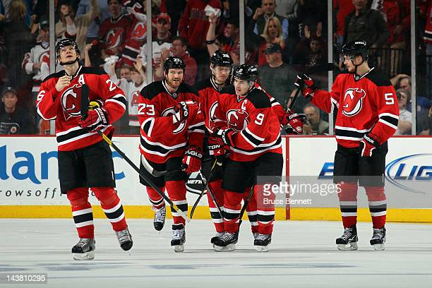 Zach Parise of the New Jersey Devils celebrates with his teammates after scoring a goal in the third period against Ilya Bryzgalov of the...