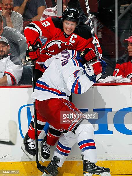Zach Parise of the New Jersey Devils is checked hard into the boards by Michael Del Zotto of the New York Rangers in Game Three of the Eastern...