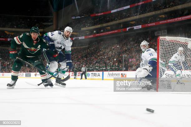 Zach Parise the Minnesota Wild and Erik Gudbranson of the Vancouver Canucks chase the puck in front of goalie Jacob Markstrom of the Vancouver...