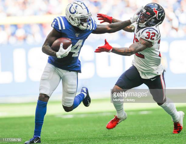 Zach Pascal of the Indianapolis Colts gives a stiff arm to Lonnie Johnson of the Houston Texans during the first half at Lucas Oil Stadium on October...