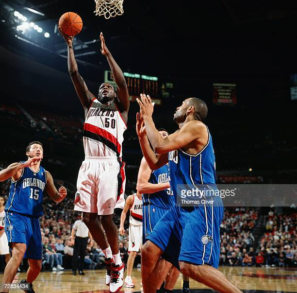 Zach Randolph of the Portland Trail Blazers takes the ball to the basket against Hedo Turkoglu and Grant Hill of the Orlando Magic at The Rose Garden...