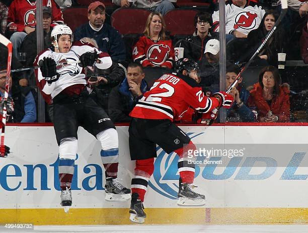 Zach Redmond of the Colorado Avalanche is hit by Jordin Tootoo of the New Jersey Devils during the first period at the Prudential Center on December...