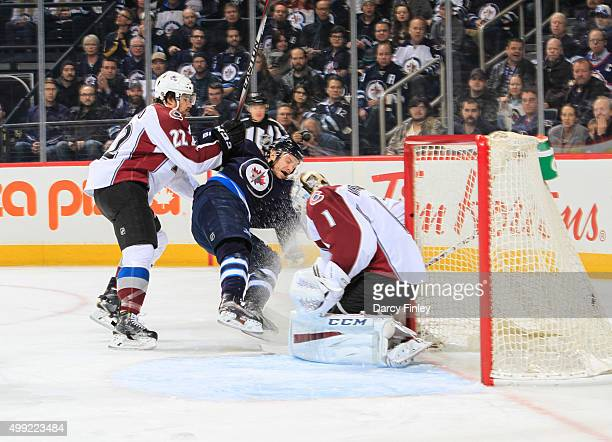 Zach Redmond of the Colorado Avalanche knocks Bryan Little of the Winnipeg Jets to the ice as goaltender Semyon Varlamov makes a save during...