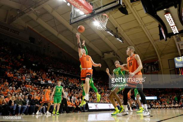 Zach Reichle of the Oregon State Beavers shoots the ball past Anthony Mathis of the Oregon Ducks during the first half at Gill Coliseum on February...