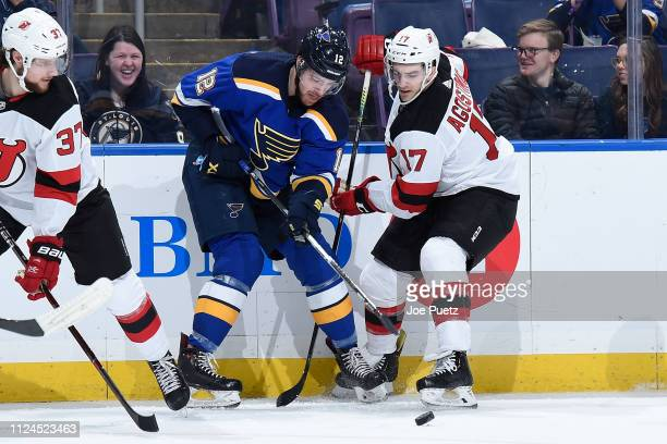 Zach Sanford of the St Louis Blues and Kenny Agostion of the New Jersey Devils battle for the puck at Enterprise Center on February 12 2019 in St...