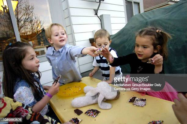 Zach Schwartz center shares a piece of chocolatecoated matzoh with Lucie Abbott right at a Passover dinner on Monday night in Superior At left is...