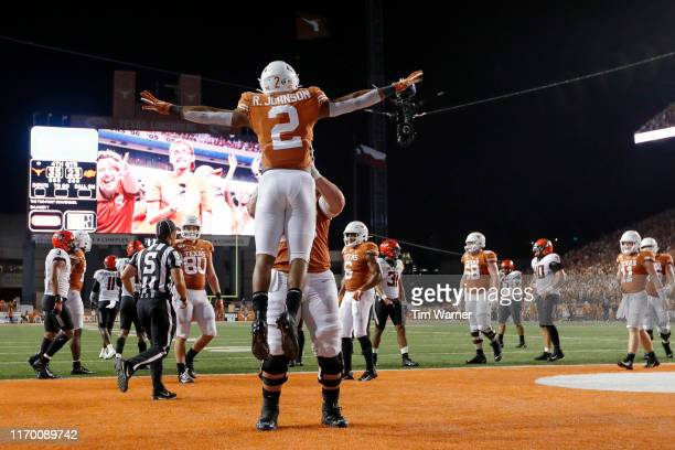 Zach Shackelford of the Texas Longhorns lifts Roschon Johnson in celebration after scoring on a two point conversion against the Oklahoma State...