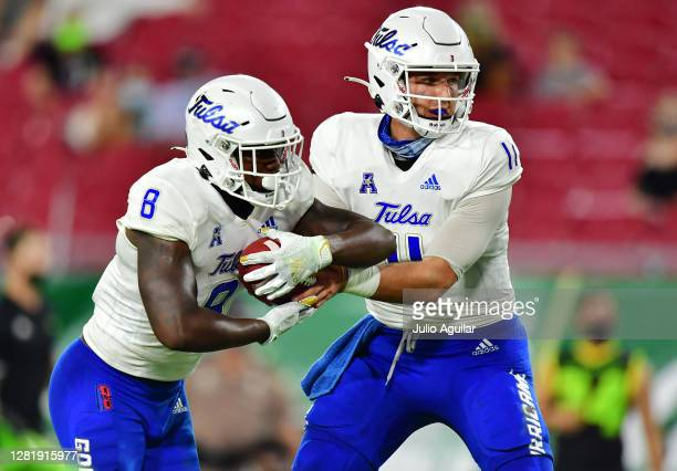 Zach Smith of the Tulsa Golden Hurricane hands the ball off to Deneric Prince of the Tulsa Golden Hurricane during the first half against the South...