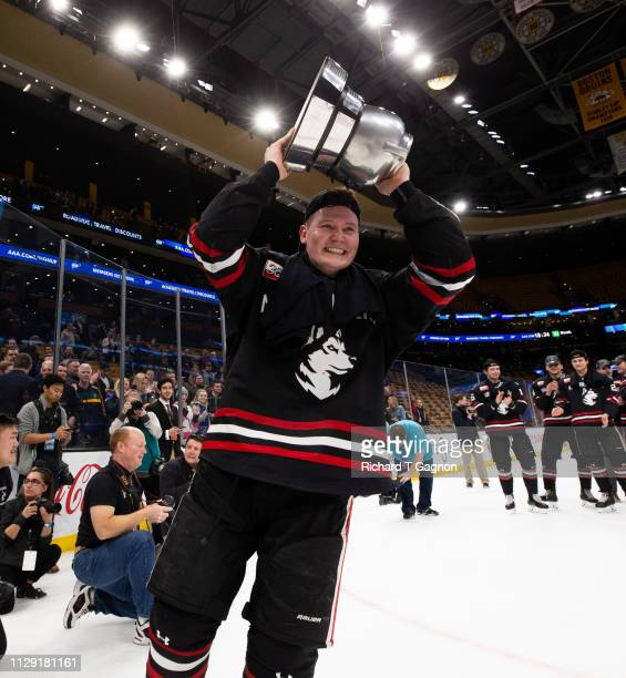 Zach Solow of the Northeastern Huskies celebrates with the Beanpot trophy after a victory against the Boston College Eagles during NCAA hockey in the...