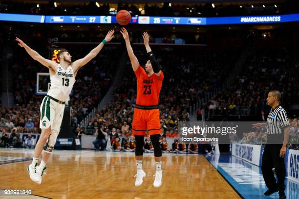 Zach Thomas of the Bucknell Bison shoots over F Ben Carter of the Michigan State Spartans during the NCAA Division I Men's Basketball Championship...