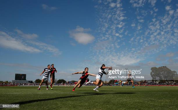 Zach Tuohy of the Cats evades Zach Merrett of the Bombers during the AFL 2018 JLT Community Series match between the Geelong Cats and the Essendon...