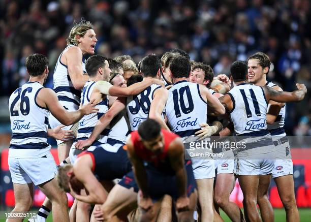 Zach Tuohy of the Cats is congratulated by team mates after kicking a goal after the siren to win the round 18 AFL match between the Geelong Cats and...